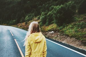 Young woman walking away on the road