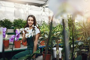 Young gardener taking a pause in her work sitting in greenhouse talking to flowers.