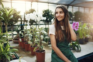 Young and beautiful female gardener sitting in a greenhouse