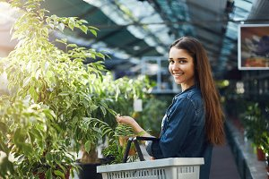 Young female shopping for plants in a greenery store looking at camera smiling.