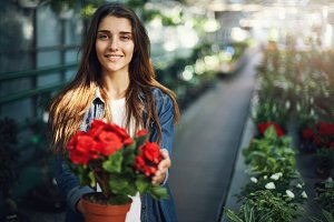 Beautiful female gardener taking care of flowers looking at camera smiling.