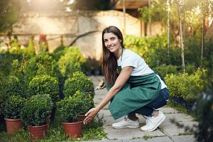 Young woman caring about small trees in backyard or a large greenery store. Looking at camera smiling.