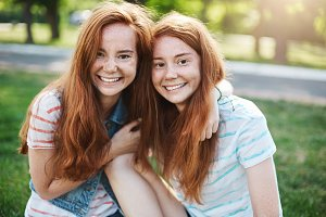 Portrait of identical ginger twin sisters smiling and having fun. Red haired rascals taking the best of their life. Friendship and youth concept.