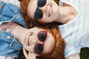 Twin ginger sisters wearing shades laying on grass on a sunny autumn day enjoying the sky. Getting grown up together in redhead madness.