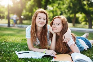 Ginger twins preparing for their exams outdoors in a city park. Learning is so much better with a best friend. Study and knowledge concept.