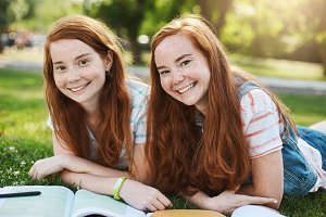 Ginger twin girls spending their summer school break to get ready to university exams. Future doctor and lawyer having fun smiling on a sunny day in park.