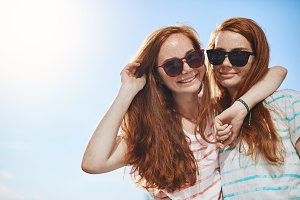 Two red head twins wearing shades. Sister girls wearing black glasses on a sunny summer day, looking at camera smiling. Having a close supporting friend is luck.