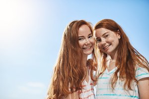 Two ginger girls looking at camera smiling on a sunny summer day. Having a twin sister is a great luck.