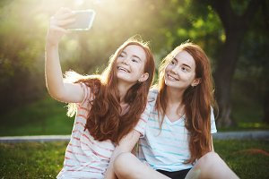 Ginger twin girls taking a selfie on a smart phone, smiling rejoicing. Modern technology connects people more than ever. Having a distant friend is so much fun.