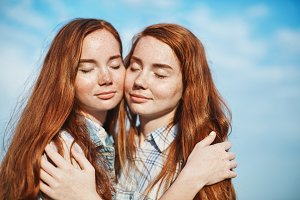 Two ginger sisters hugging each other on a bright sunny day sharing their warmth and emotions with each other.