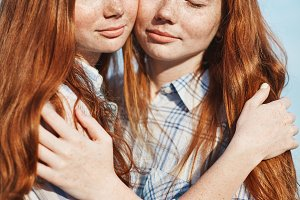 Portrait of red haired twin sisters hugging each other. Family relationships and friendship are the life goal.