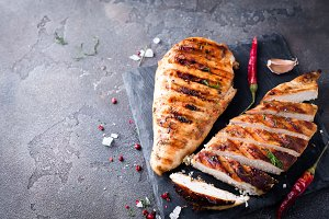 Grilled chicken fillets on slate plate.