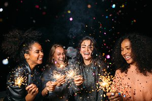 Laughing friends with sparklers