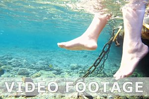 Woman is swinging her legs in tropical sea water