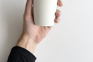 Hand holding coffee cup isolated