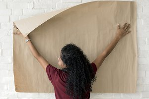 Woman putting paper on wall