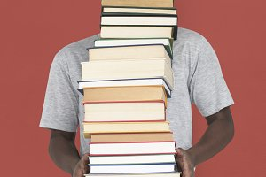 Man holding pile of books