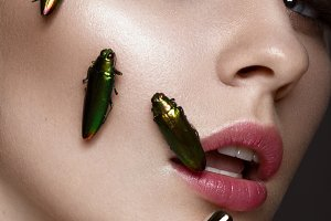 Portrait of beautiful girl with colorful make-up and cockroaches. Beauty face.