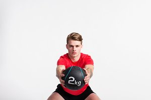 Fitness man holding medicine ball, doing squat, studio shot.