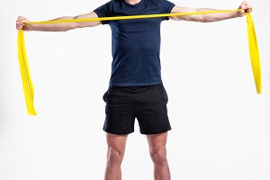 Fitness man working out with resistance bands, studio shot.