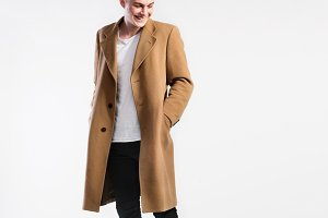 Young handsome hipster man in brown coat, studio shot.