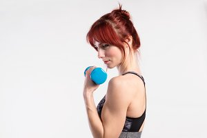 Attractive young fitness woman working out with barbell. Studio