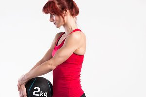 Fitness woman in red tank top holding medicine ball. Studio shot