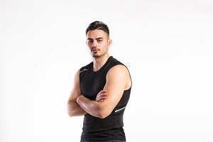 Young fitness man in black sleeveless shirt , studio shot.
