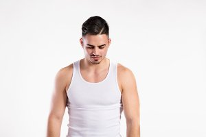 Young fitness man in white sleeveless shirt , studio shot.