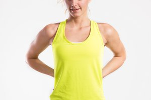 Attractive young fitness woman in yellow tank top. Studio shot.