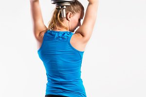 Attractive young fitness woman holding dumbell. Studio shot.