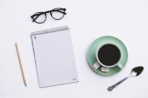 Notepad and Cup of coffee on wooden background.