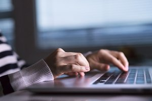 Hands of unrecognizable woman sitting at desk working on laptop.