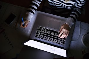 Unrecognizable woman sitting at desk working on laptop.