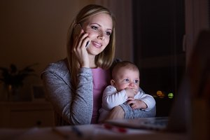 Mother with son in the arms, making phone call