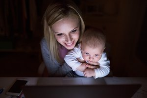 Mother with son in the arms, laptop in front of her