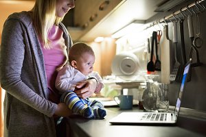 Unrecognizable mother with son in the arms, laptop on kitchen co