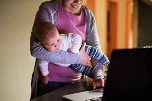Unrecognizable mother with son, working on laptop