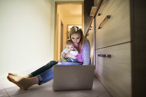 Beautiful mother with son in the arms, working on laptop.