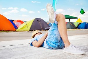 Unrecognizable on summer music festival, lying on concrete path.