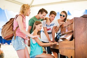 Teenagers at summer music festival, girl plays the piano