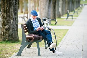 Senior man with bicycle in town, holding smart phone, texting