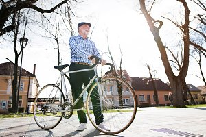 Senior man in blue checked shirt with bicycle in town.