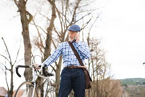 Senior man with smartphone and bicycle in town.