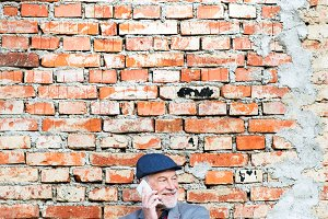 Senior man with smartphone making phone call against brick wall.