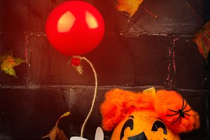Scary red hair clown made from pumpkin, holding red balloon