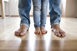 Beautiful young family. Bare feet of father and daughter.