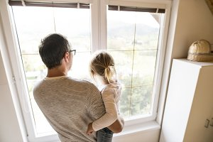 Father with little daughter standing at the window.