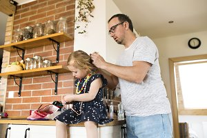 Young father at home styling hair of his little daughter.