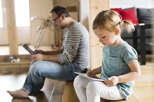 Father with laptop and little daughter with tablet at home.